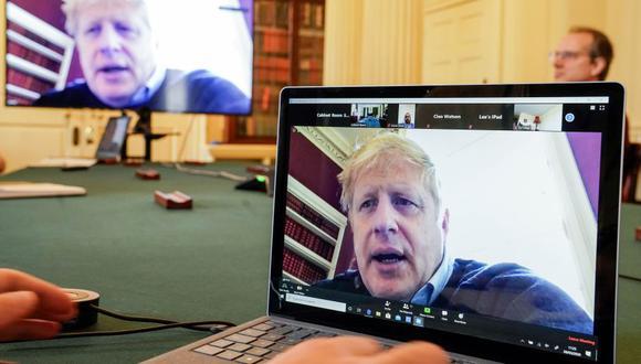 Esta foto del 28 de marzo del 2020, muestra una imagen del primer ministro británico, Boris Johnson, en una pantalla de computadora mientras preside de forma remota una reunión sobre el coronavirus. Johnson está confinado desde que diera positivo el 27 de marzo de COVID-19, tras presentar síntomas leves. (Foto: AFP)