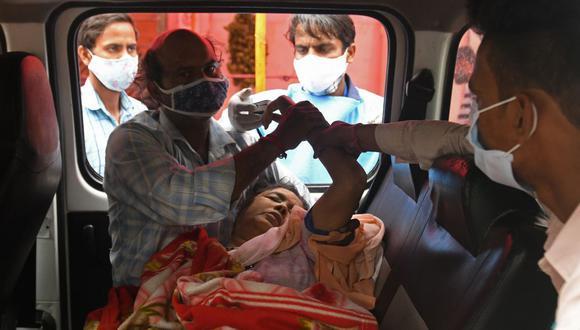 Los miembros de una familia atienden a una mujer inconsciente dentro de una camioneta en un centro de soporte de oxígeno gratuito para pacientes de coronavirus en Nueva Delhi, India. (Foto de Arun SANKAR). / AFP).