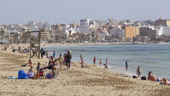 Los turistas toman el sol en la playa de Palma en Palma de Mallorca, España, el 29 de marzo de 2021. (JAIME REINA / AFP).