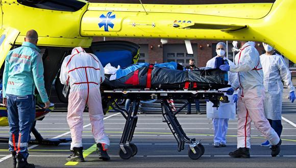 Personal médico lleve en camilla a un paciente infectado con coronavirus covid-19 para una evacuación en helicóptero desde el Hospital Flevo en Almere, a Munster, Alemania, el 23 de octubre de 2020. (Foto de Olaf Kraak / ANP / AFP).