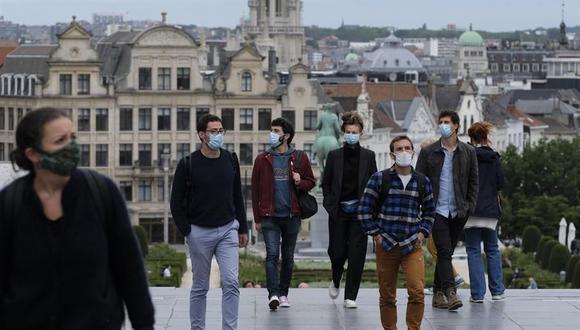Varias personas con mascarilla para protegerse del coronavirus pasan por la Grand Place de Bruselas. (EFE/EPA/OLIVIER HOSLET).