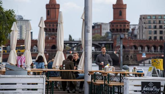 En esta foto de archivo tomada el 10 de octubre de 2020, la gente se sienta en una terraza con vista al río Spree y al Oberbaumbruecke en Berlín. (Foto: AFP)