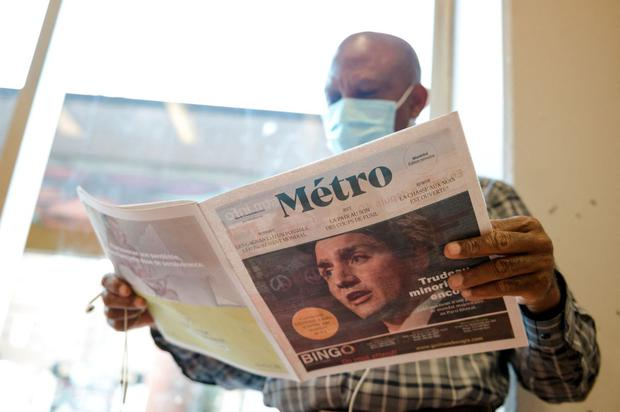 A man reads a newspaper with a cover image of Canadian Prime Minister Justin Trudeau.  (Andrzej Ivanov / AFP).