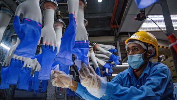 Un trabajador inspecciona guantes desechables en la fábrica Top Glove en Shah Alam, en las afueras de Kuala Lumpur (Malasia), el 26 de agosto de 2020. (Mohd RASFAN / AFP).
