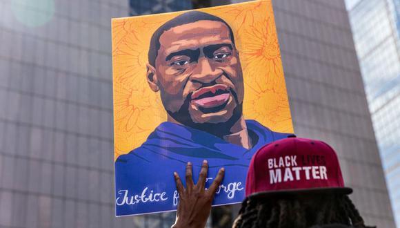 En esta foto de archivo, los manifestantes sostienen carteles en honor a George Floyd y otras víctimas del racismo mientras se reúnen durante una protesta frente al Centro de Gobierno del Condado de Hennepin, el 28 de marzo de 2021, en Minneapolis, Minnesota (Estados Unidos). (Kerem Yucel / AFP).