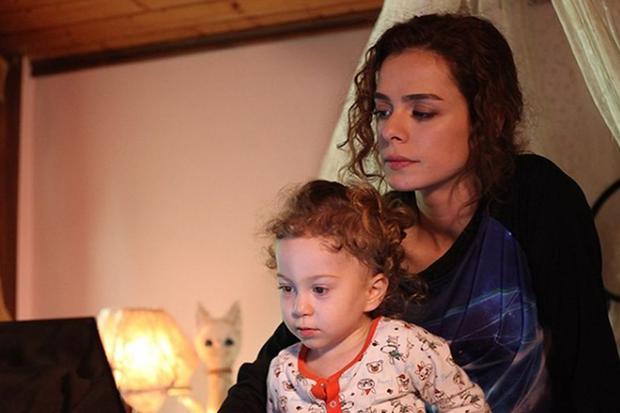 Zeynep Taskin tiene a su hijo entre sus brazos, mientras ven la computadora en su habitación (Foto: Süreç Film)