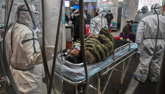 Esta foto de archivo tomada el 25 de enero de 2020 muestra a miembros del personal médico con ropa protectora que llevan a un paciente al Hospital de la Cruz Roja de Wuhan durante el inicio de la pandemia de coronavirus. (Foto de Hector RETAMAL / AFP).