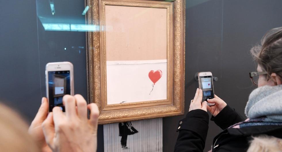 El artista callejero causó sensación en octubre cuando hizo que una obra suya quedara parcialmente rasgada instantes después de haberse vendido en una millonaria subasta. (Fotos: AFP)