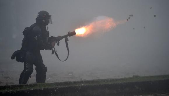 La policía antidisturbios lanza gases lacrimógenos contra los manifestantes durante los enfrentamientos en Cali, Colombia, el 3 de mayo de 2021. (Foto de Luis ROBAYO / AFP).