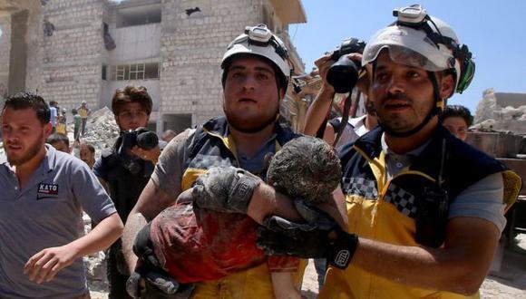 Miembros del equipo de defensa civil de Siria, conocidos como cascos blancos, rescataron vivo a un niño que resultó herido durante un bombardeo de Rusia en la provincia de Idlib. Foto: AFP, vía BBC Mundo
