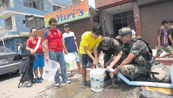 Vecinos afectados por el corte del servicio llevan agua de un reservorio de plástico colocado por Indeci. (Fernando Sangama / El Comercio)