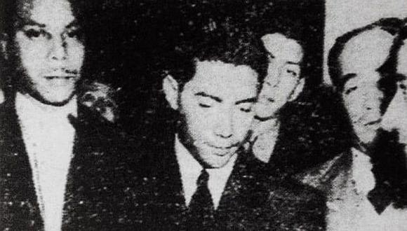 Rodeado de investigadores aparece el criminal Juan Perazo Cáceres, al centro, vestido de negro y con la cabeza baja. Terminaba de confesar su crimen en la Dirección General de Investigaciones. (Foto: Archivo Histórico El Comercio)