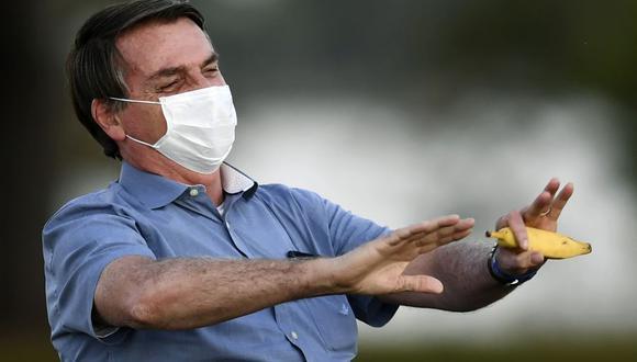 Coronavirus: Jair Bolsonaro sostiene un plátano mientras habla con sus partidarios en el jardín del Palacio Alvorada en Brasilia, el 24 de julio de 2020. (Foto: EVARISTO SA / AFP).