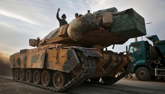 Los combatientes sirios pro-turcos viajan en un tanque del ejército cerca de la aldea turca de Akcakale a lo largo de la frontera con Siria. (AFP / Bakr ALKASEM).