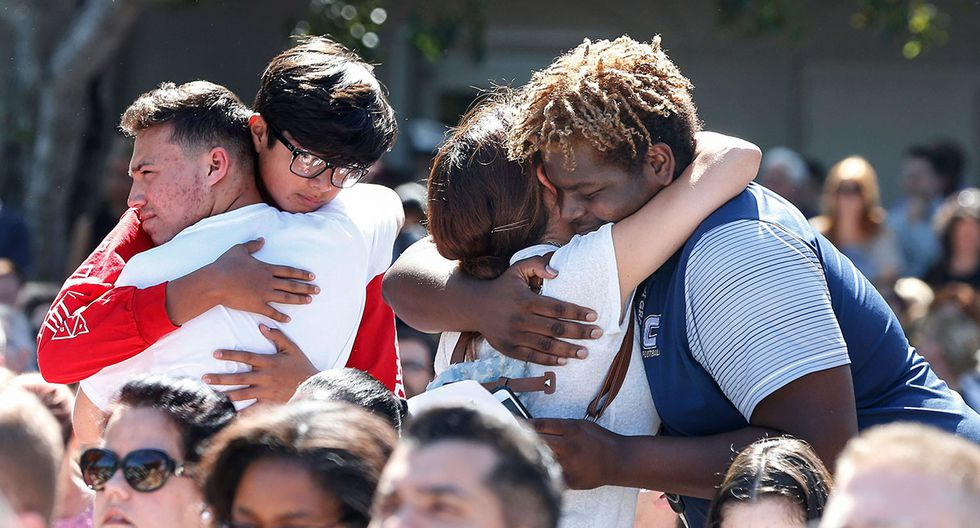Mourners hug during a prayer vigil for the victims of the Marjory Stoneman Douglas High School shooting at Parkridge Church in Coral Springs, Florida on February 15, 2018.  The heavily armed teenager who gunned down students and adults at a Florida high school was charged Thursday with 17 counts of premeditated murder, court documents showed.Nikolas Cruz, 19, killed fifteen people in a hail of gunfire at Marjory Stoneman Douglas High School in Parkland, Florida. Two others died of their wounds later in hospital, the sheriff's office said.  / AFP / RHONA WISE