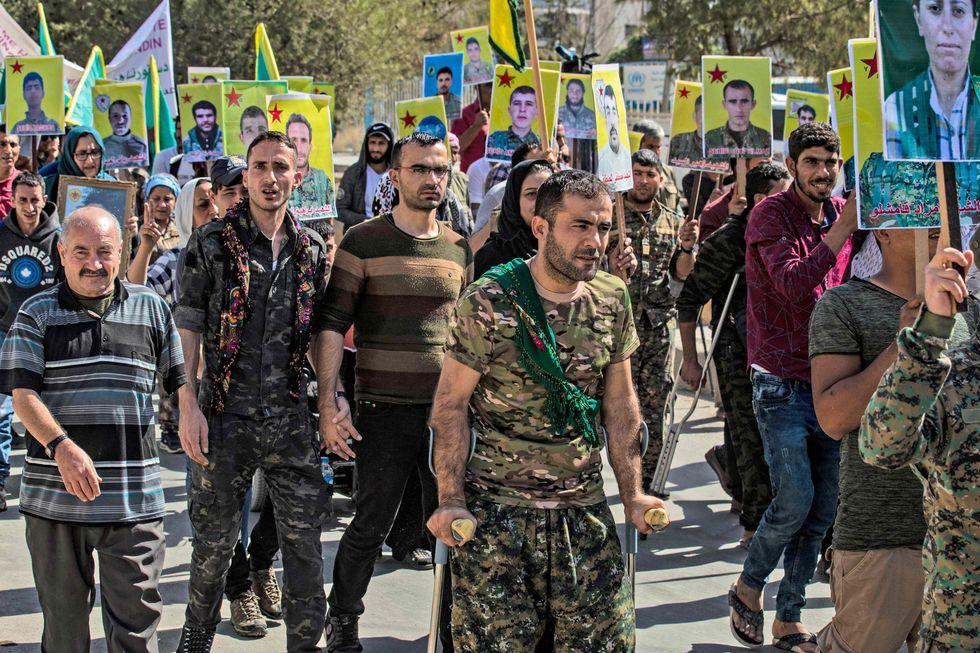Los combatientes y veteranos de las Unidades de Protección de la Mujer Kurda (YPJ) y las Unidades de Protección del Pueblo (YPG) marchan en la ciudad de Qamishli, en el norte de Siria. (AFP / Delil SOULEIMAN).