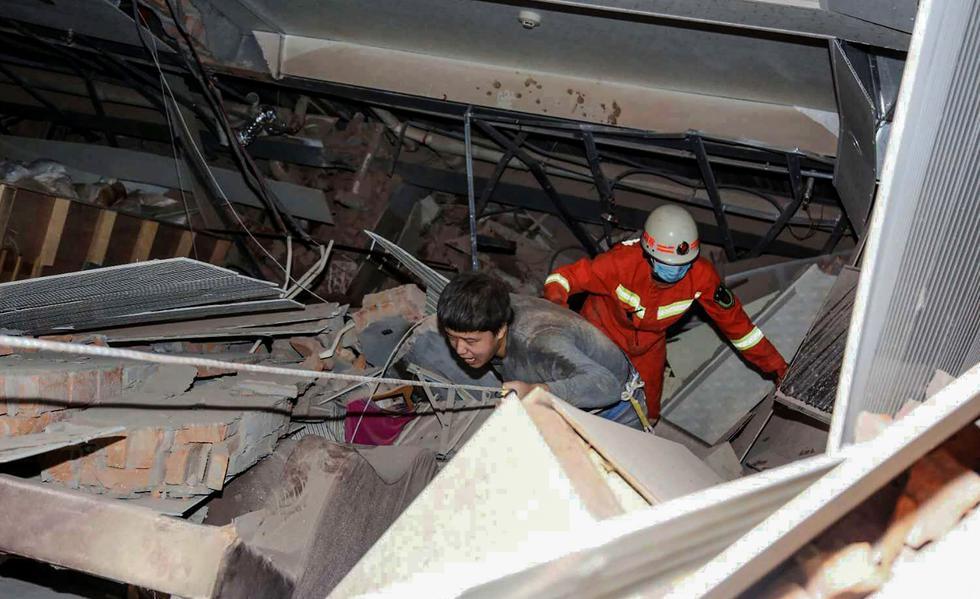 Los rescatistas ayudan a un hombre que estaba atrapado entre los escombros de un hotel derrumbado en Quanzhou, en la provincia oriental china de Fujian. En este lugar había personas en cuarentena por el coronavirus. (AFP).