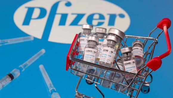 """Una pequeña canasta de compras llena de viales etiquetados como """"COVID-19  y un logotipo de Pfizer. (REUTERS / Dado Ruvic / Ilustración)."""