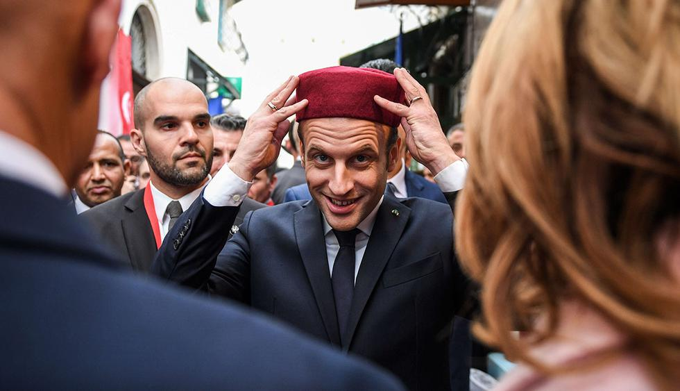 TOPSHOT - French President Emmanuel Macron (C) tries on a fez during his tour of the Medina (old town) of the Tunisian capital Tunis on February 1, 2018, during Macron's first state visit to the North African country.  / AFP / POOL / Eric FEFERBERG