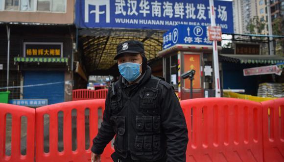 Un oficial de policía de China hace guardia fuera del mercado mayorista de mariscos de Huanan, donde se detectó el coronavirus en Wuhan, el 24 de enero de 2020. (Foto de Hector RETAMAL / AFP).