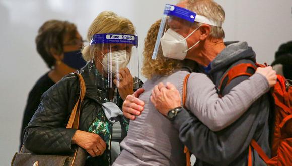 Viajeros con mascarillas y protectores faciales se despiden de sus familiares antes de tomar sus vuelos en el aeropuerto de Denver, Colorado. (Reuters)