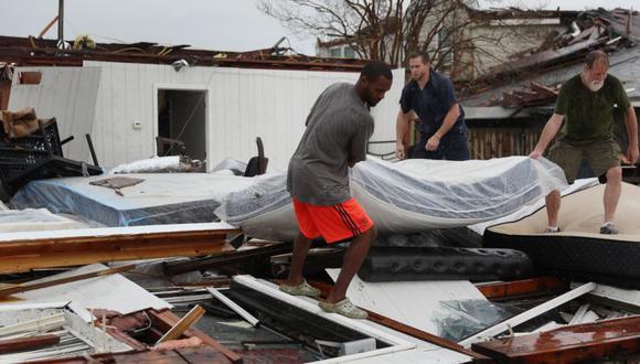 Butch Segura (R) y su hijo Stew Segura le dan un colchón a Janero Jones después de que su tienda Mattress Doctor fuera destruida cuando el huracán Laura pasó por el área en Lake Charles, Louisiana. (Foto: AFP / ANDREW CABALLERO-REYNOLDS).