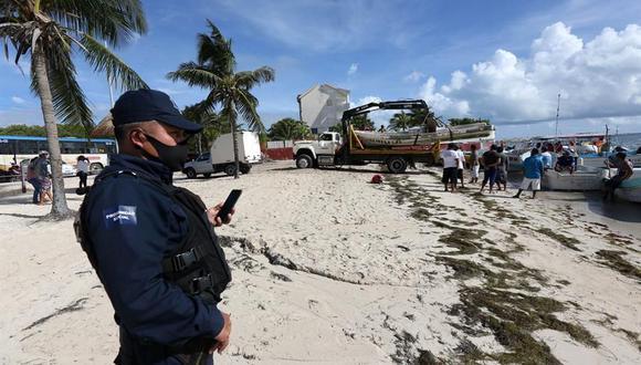 Pescadores y prestadores de servicios trabajan en el retiro de embarcaciones que podrían colapsar con la llegada del huracán Delta a Cancún, estado de Quintana Roo (México). (EFE/ Alonso Cupul).