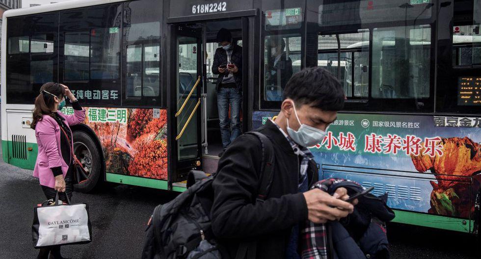 Los residentes se bajan de un autobús en Wuhan, en la provincia central de Hubei, en China. (AFP)