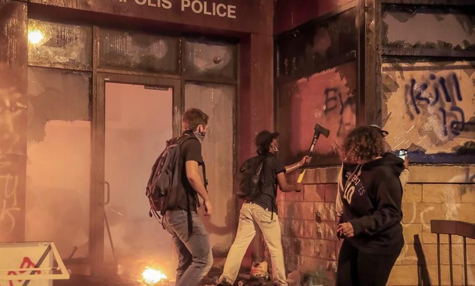 Manifestantes destruyen los vidrios de una comisaría de Minneapolis después de haberla incendiado durante las protestas por la muerte de George Floyd a manos de policías. (EFE / EPA / TANNEN MAURY).