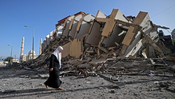 Una mujer palestina pasa frente a un edificio destruido en la ciudad de Gaza. (Foto de MOHAMMED ABED / AFP).