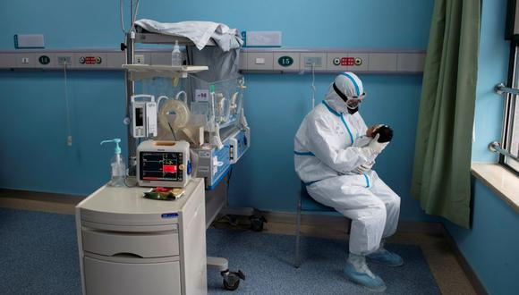 Imagen referencial. Una enfermera con traje protector atiende a un bebe con COVID-19, causado por el coronavirus, en una sala de aislamiento. (REUTERS).