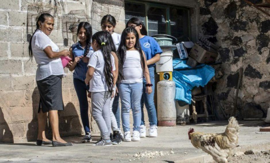Jocelyn, Vanesa y Diana Ramirez, niños de origen mexicano nacidos en Estados Unidos, hablan por teléfono con su madre, que está en Estados Unidos, durante una reunión familiar organizada por una ONG en Teopantlán, (Foto: AFP)