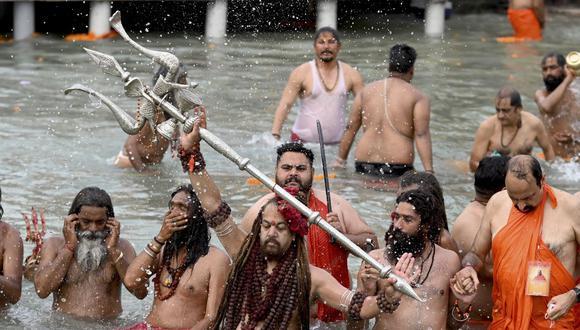 Los sadhus (hombres santos hindúes) se bañan en las aguas del río Ganges el día de Shahi Snan (baño real) durante el festival religioso en curso Kumbh Mela, en medio de la pandemia de coronavirus. (Foto de Money SHARMA / AFP ).