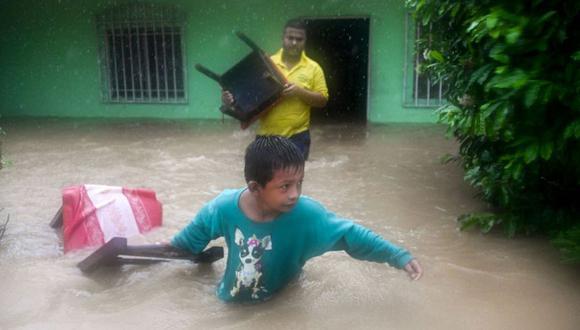 Un niño y un hombre salvan sillas de una casa inundada debido a las fuertes lluvias causadas por el huracán Eta, ahora degradado a tormenta tropical, en Puerto Barrios, Izabal 310 km al norte de la Ciudad de Guatemala. (Foto: AFP / Johan ORDONEZ).