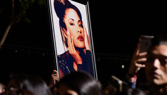 Los fanáticos muestran una foto de Selena durante la ceremonia en honor a la cantante con una estrella en el Paseo de la Fama de Hollywood el 3 de noviembre de 2017, en Hollywood, California. (Foto:AFP)