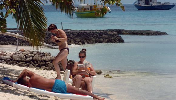 En esta foto de archivo, los turistas extranjeros se relajan en una playa en la isla Kurumathi, al oeste de la capital de Maldivas, Male. (Foto de LAKRUWAN WANNIARACHCHI / AFP).