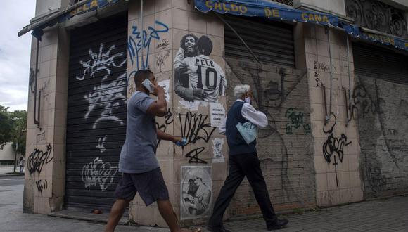 Hombres caminan frente a la pared de un bar cerrado con un grafitti del fallecido cantante jamaicano Bob Marley y el exfutbolista brasileño Pele abrazándose, en el área del puerto en Río de Janeiro, Brasil, el 8 de diciembre de 2020. (MAURO PIMENTEL / AFP).