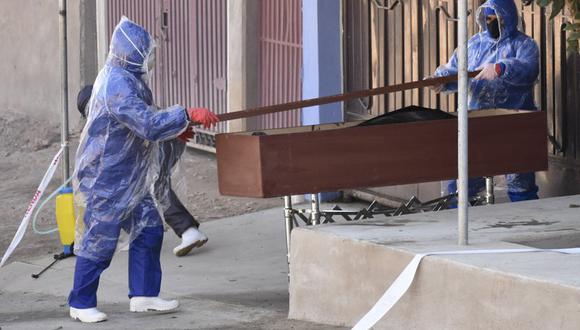 Trabajadores ponen el cadáver de un hombre envuelto en una bolsa de plástico dentro de un ataúd en una calle de Cochabamba, Bolivia, el domingo 5 de julio de 2020. Según un familiar, el hombre murió con síntomas aparentes de coronavirus mientras salía de su casa a busca un doctor. (AP Foto/Dico Solis).