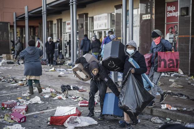 Looters take some items in a vandalized shopping center in Vosloorus, South Africa, on July 14, 2021.