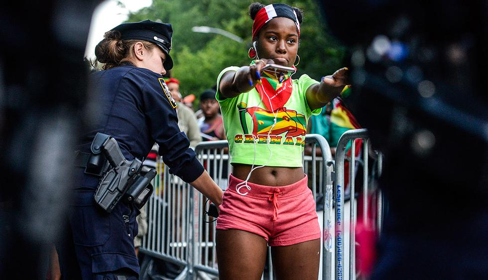 NEW YORK, NY - SEPTEMBER 4: Revelers are searched by police officers during a Caribbean street carnival called J'ouvert on September 4, 2017 in New York City. J'ouvert, which draws tens of thousands of costumed celebrants, has been plagued by violence in recent years resulting in new intensive security measures.  Stephanie Keith/Getty Images/AFP