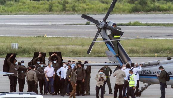 El presidente de Colombia, Iván Duque (izquierda), camina rodeado de guardaespaldas cerca del helicóptero presidencial en la pista del Aeropuerto Internacional Camilo Daza luego de que fuera alcanzado por disparos en Cúcuta, el 25 de junio de 2021. (Schneyder MENDOZA / AFP).