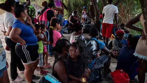 Los migrantes, muchos de ellos haitianos, se sientan a orillas del río Grande antes de cruzar la frontera entre México y Estados Unidos en Ciudad Acuña, estado de Coahuila, México. (Foto: PEDRO PARDO / AFP).