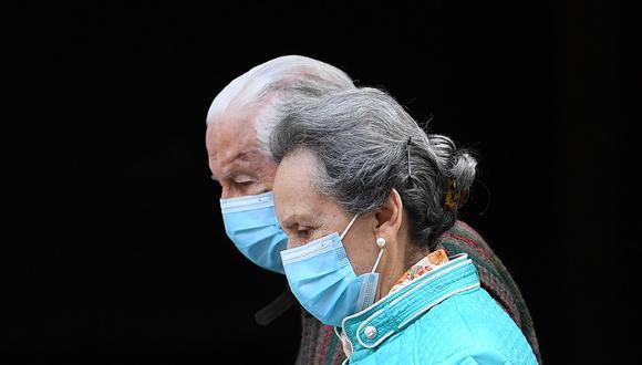 Una pareja de ancianos con máscaras faciales camina en Madrid el 30 de abril de 2020 durante un cierre nacional para evitar la propagación de la enfermedad COVID-19. (Foto: AFP/Gabriel BOUYS)