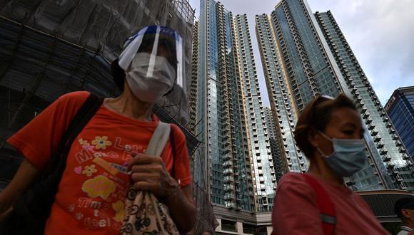 Los peatones pasan por el complejo de edificios residenciales Grand Central en Hong Kong el 28 de mayo de 2021, en medio de la pandemia de coronavirus. (Foto de Anthony WALLACE / AFP).