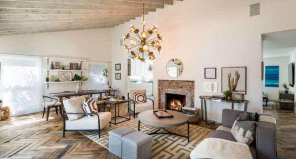El blanco se extiende por todos los ambientes de la casa. Aquí destaca una lámpara de estilo sputnik, una alfombra con tramas geométricas, composiciones de cuadros y una chimenea que hace más acogedor el lugar. (Foto: themls.com)