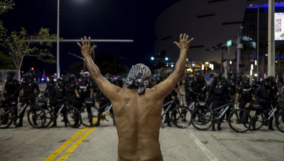 Un manifestante levanta las manos frente a una fila de policías durante un mitin en respuesta a la reciente muerte de George Floyd, un hombre negro desarmado que murió mientras estaba bajo custodia policial en Minneapolis, en Miami, Florida, el 31 de mayo de 2020.  (Foto: Ricardo ARDUENGO / AFP)