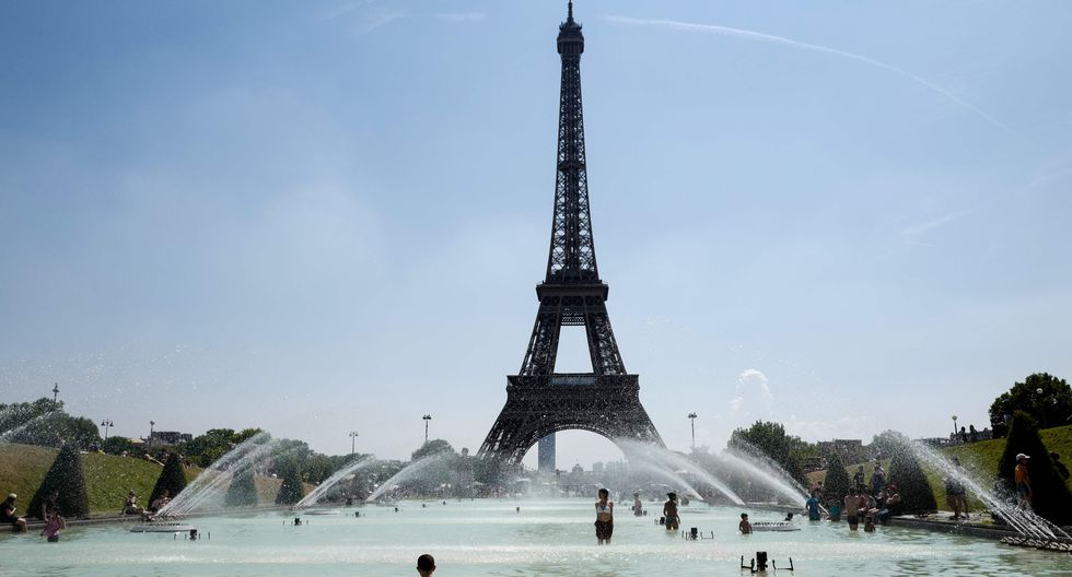 Las personas se refrescan en la Fuente del Trocadero frente a la Torre Eiffel en París.(Foto: AFP)