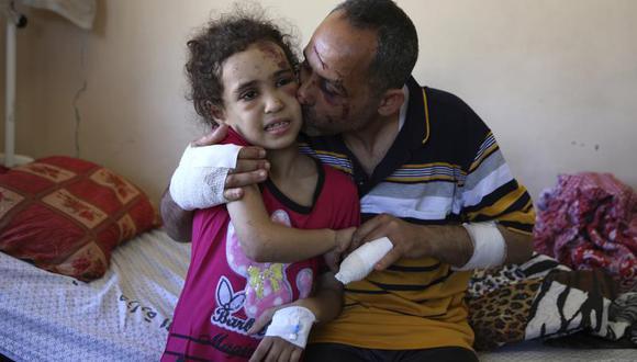Suzy Ishkontana, de 7 años, recibe un beso de su padre Riad Ishkontana, de 42 años, en el Hospital Shifa en Ciudad de Gaza, el martes 18 de mayo de 2021. (AP Foto/Abdel Kareem Hana).
