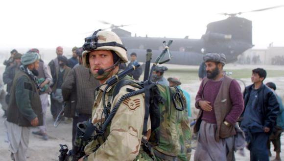 En esta foto de archivo tomada el 15 de noviembre de 2001, un soldado de Operaciones Especiales de la Fuerza Aérea de estados Unidos Hace guardia cerca de un helicóptero Chinook mientras civiles afganos y milicianos leales a la rebelde Alianza del Norte observan en Kwaja Bahuddine. (Foto de BRENNAN LINSLEY / POOL / AFP).