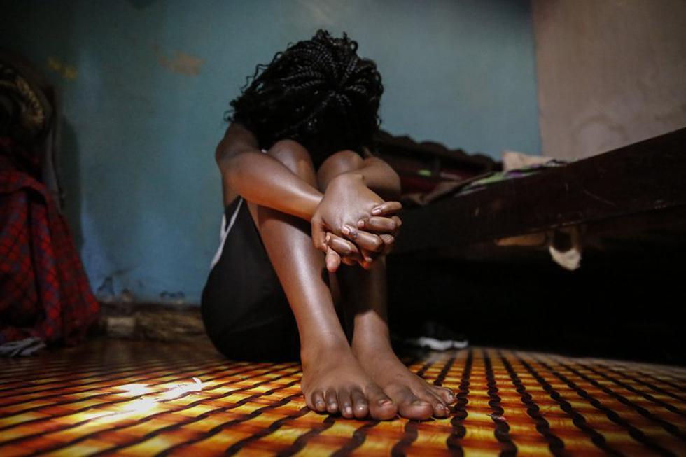 """Una adolescente que se prostituyó para ayudar a su familia en medio de la pandemia del coronavirus oculta su rostro al ser fotografiada en la habitación de Nairobi que comparte con dos amigas que siguieron el mismo camino. """"Llegamos a los 16 años sin quedar embarazadas e íbamos a la escuela. Éramos chicas ejemplares en nuestro barrio"""", cuenta la muchacha. (AP Photo/Brian Inganga)."""